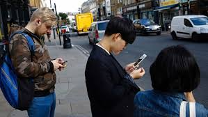 People on the street looking at their phones with their head and neck down and forward.